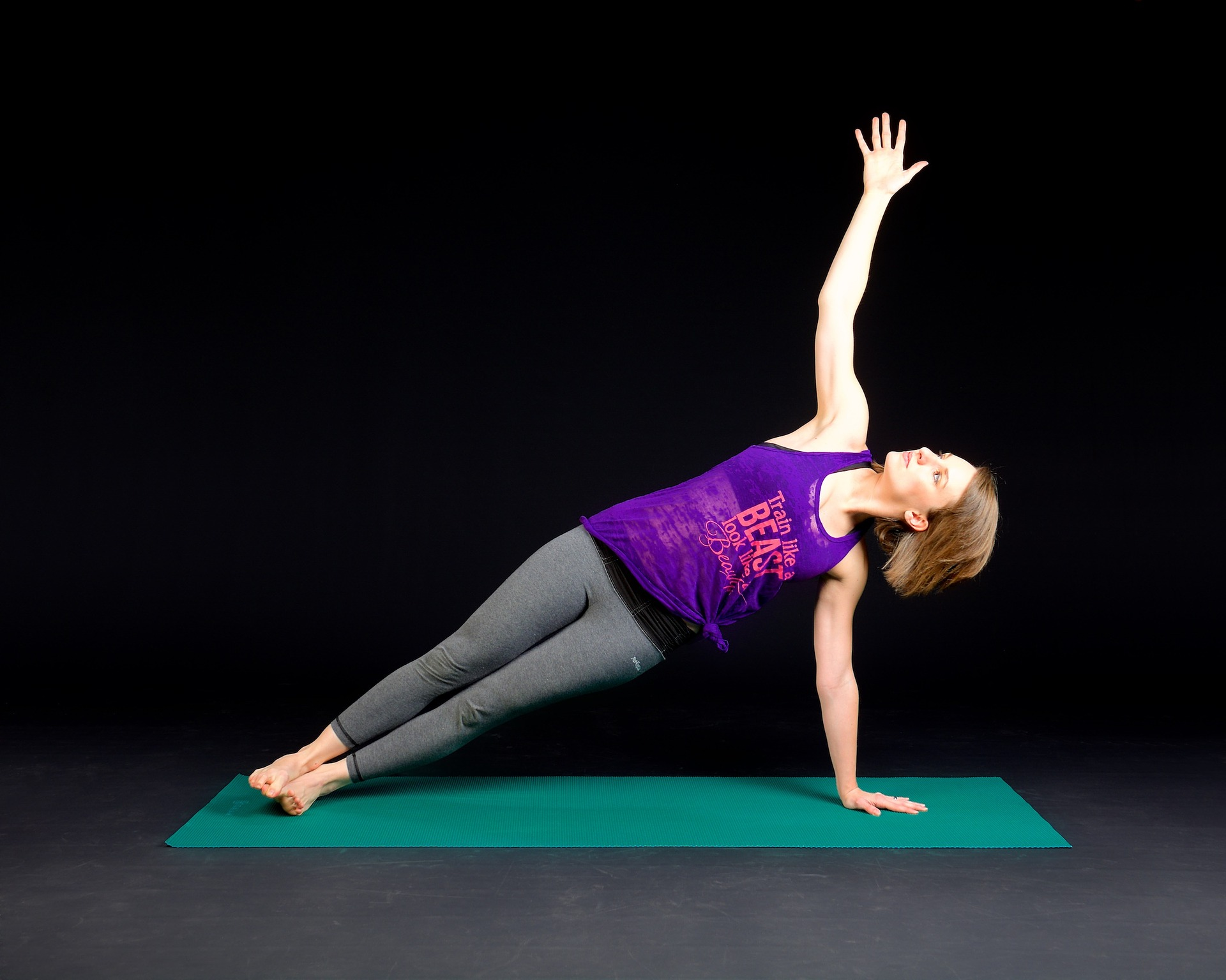 Picture of a young woman holding a side-plank pose with one arm extended upward towards the sky. Amniofix therapy provided by Karlfeldt Center of Meridian, Idaho.