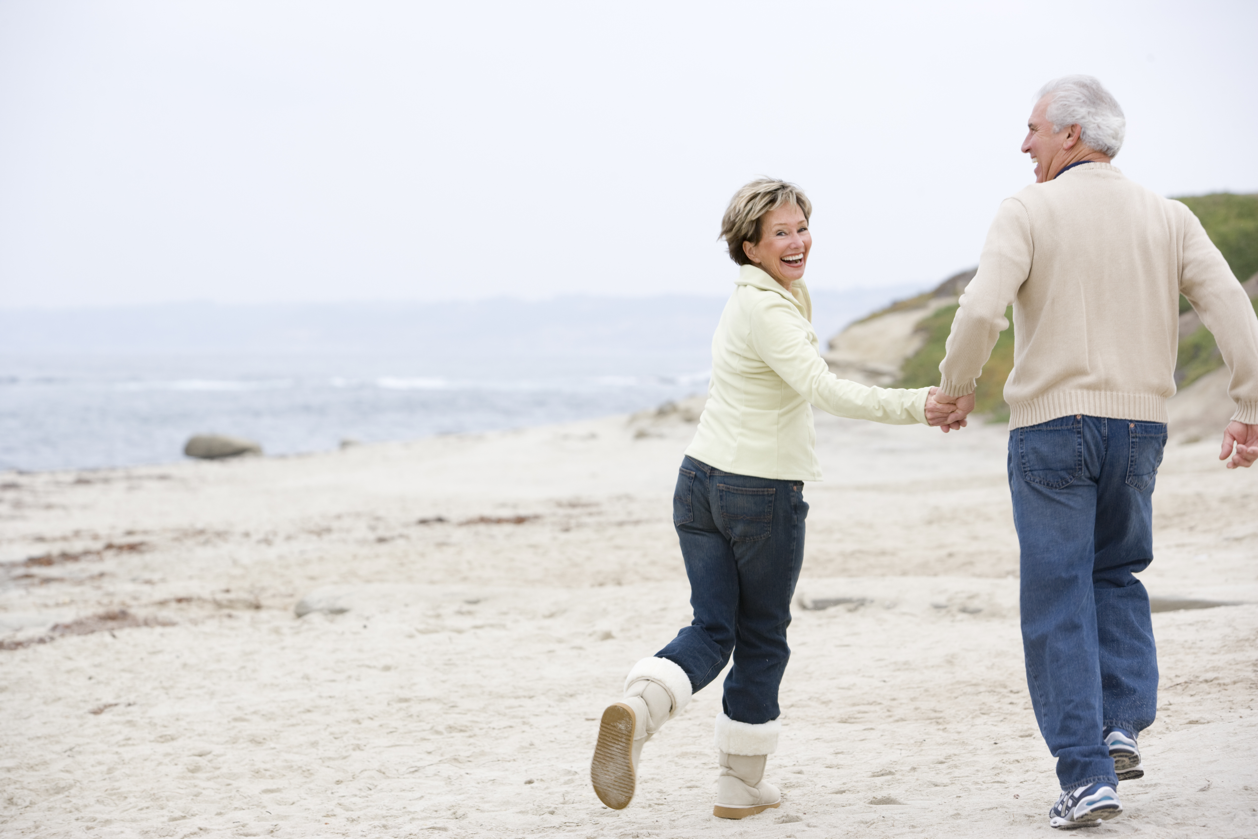 Image of an elderly couple running down the beach with smiles on their faces. Stem Cell Therapy offered at the Karlfeldt Center in Meridian, Idaho.