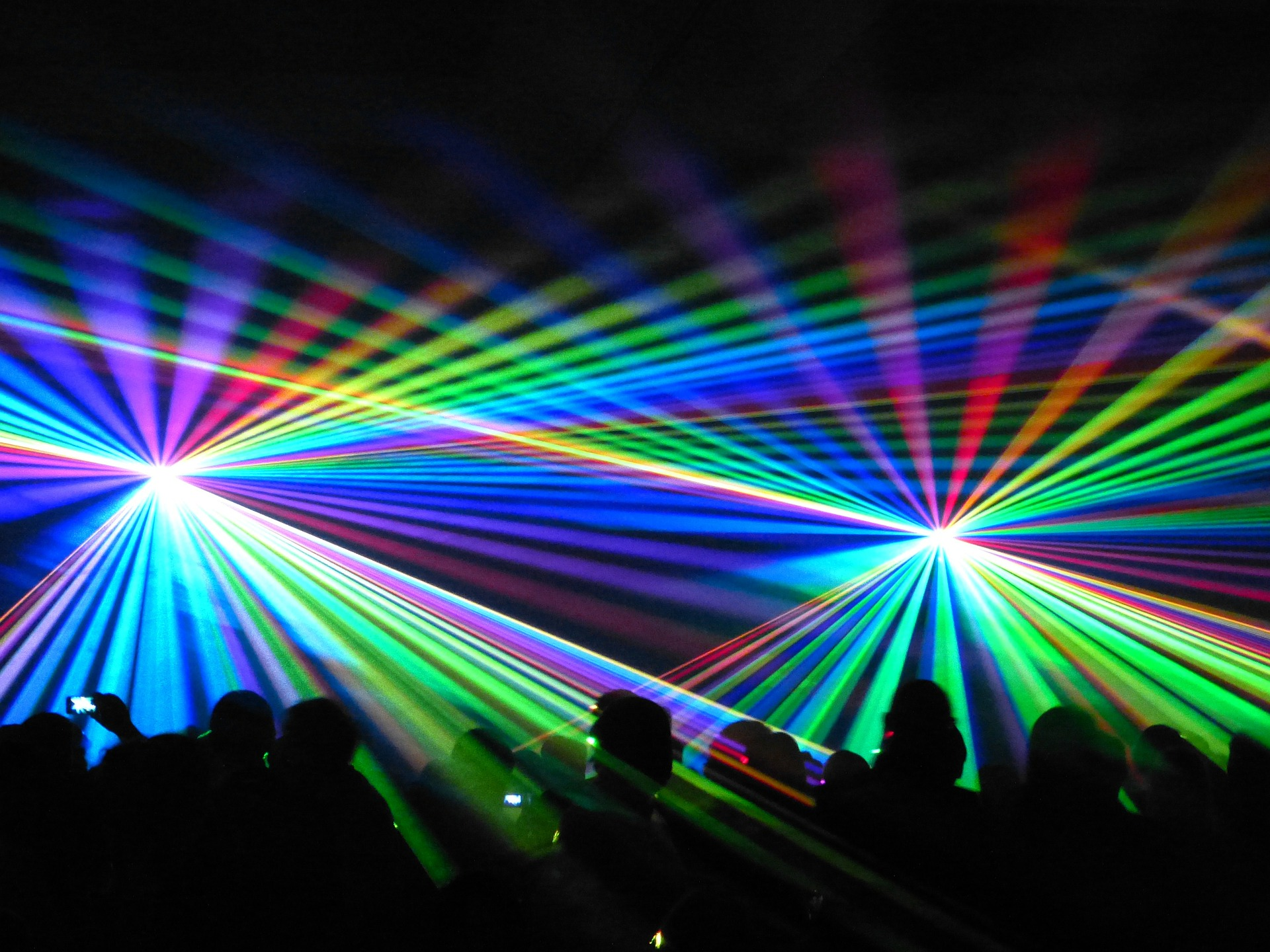 Image of a crowd with multi-colored light beams spanning across the crowd. Cold Laser Therapy offered at the Karlfeldt Center of Meridian, Idaho.